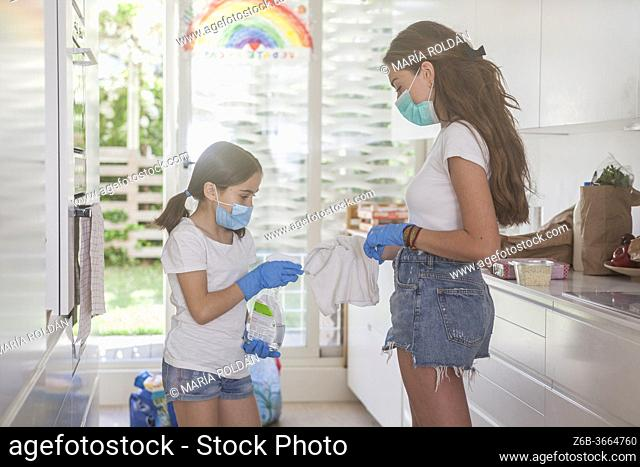 mom and daughter wearing masks and gloves with cleaner