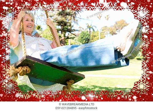 Composite image of mature couple at swing in the park