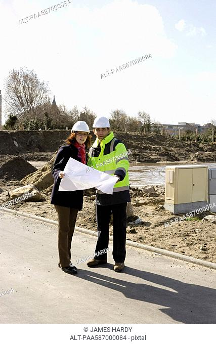 Architect and building contractor discussing blueprint at construction site