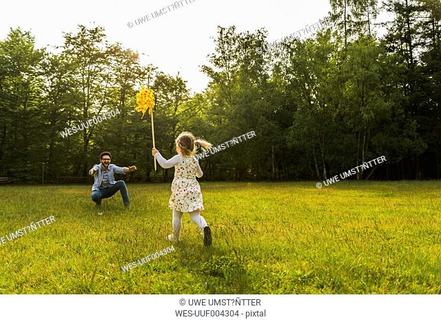 Girl with paper windmill running towards father on meadow