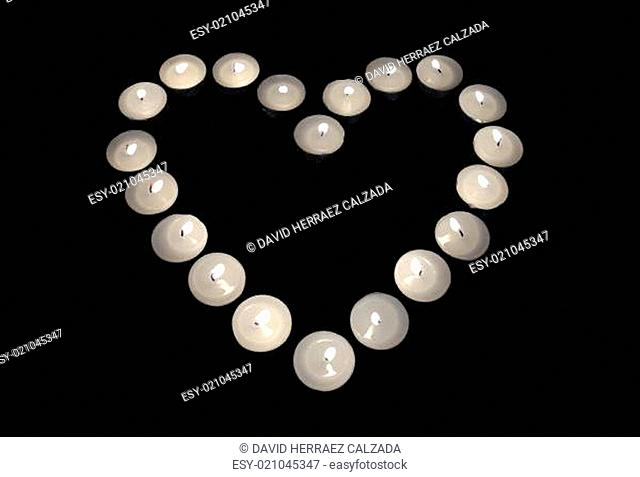 Group of burning candles forming a heart on black isolated background. Concept for St. Valentine