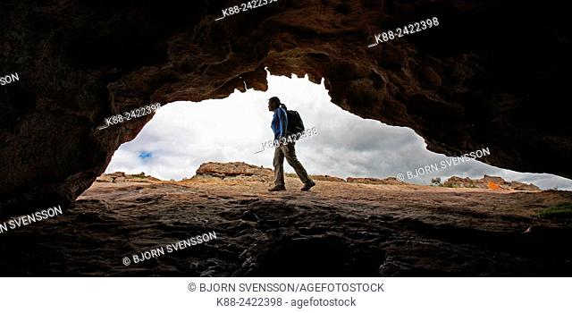 Hiker outside a cave in the northern Grampians. Victoria, Australia