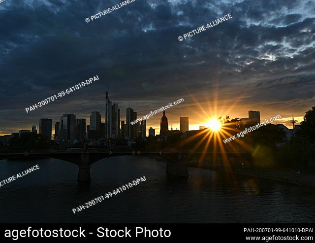 01 July 2020, Hessen, Frankfurt/Main: The sun sets in the evening behind the skyline of the banking city. Photo: Arne Dedert/dpa