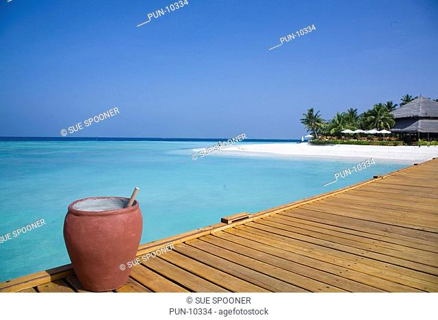 Bridge from water bungalows to Filitheyo Island in Maldives with ceramic pot full of water for washing sand off your feet