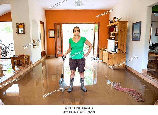 Hispanic woman shoveling water out of flooded house