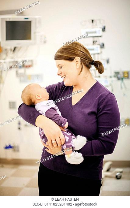 Mother standing in hospital ward holding baby son (6-11 months)