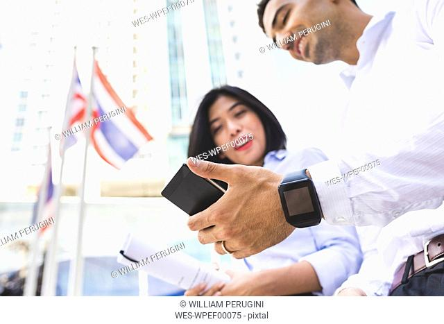 Thailand, Bangkok, businessman and businesswoman in the city with cell phone and smartwatch