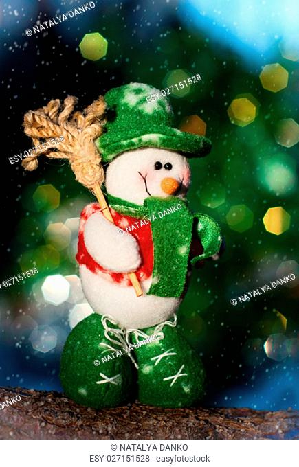 Textile snowman on a log, blurred background with a large multi-colored bokeh