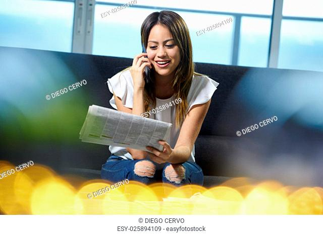Young unemployed female doing job hunting and reading employment announcements. The girl is sitting on her sofa holding a newspaper and does a phone call to...