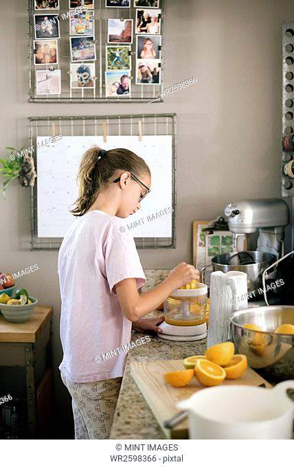 Family preparing breakfast in a kitchen, girl squeezing oranges