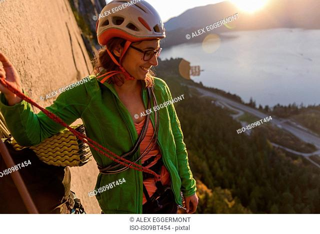 Young female rock climber looking down from The Chief at sunset, Squamish, British Columbia, Canada
