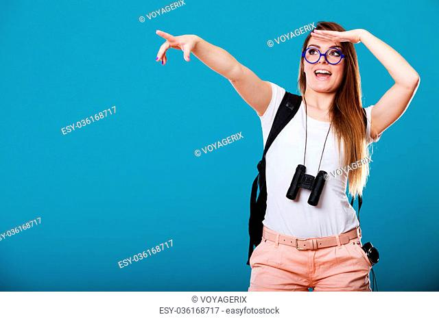 Summer holidays and tourism concept. Attractive woman long hair with backpack binocular pointing copyspace with finger on blue