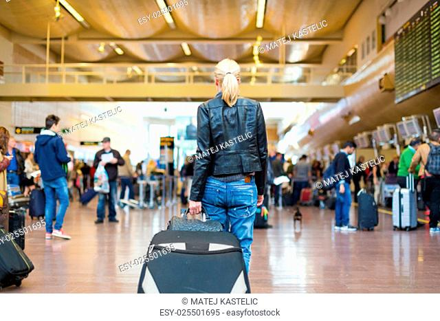Casually dressed young stylish female traveller walking the airport terminal hall draging suitcase and a handbag behind her. Blured background
