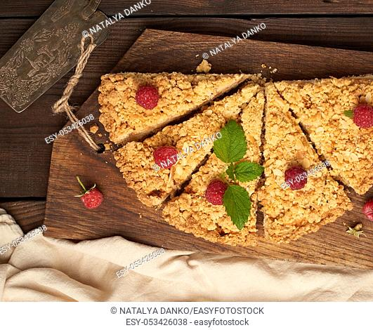 sliced triangular pieces of crumble pie with apples on a brown wooden board, top view
