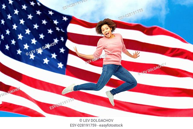 people, motion and action concept - happy african young woman jumping over american flag background