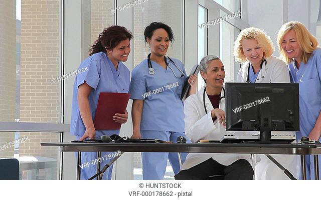 Female doctor at computer consulting with hospital staff