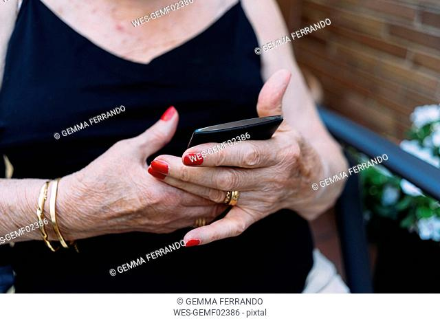 Hands of senior woman using smartphone