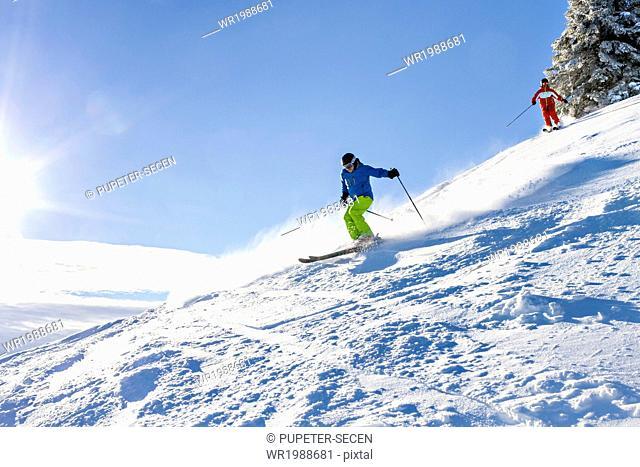 Ski holiday, Two skiers carving downhill, Sudelfeld, Bavaria, Germany