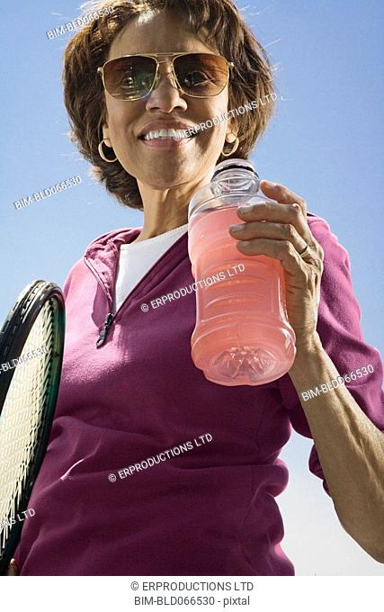 African woman drinking juice with tennis racquet