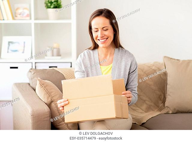 delivery, mail and people concept - smiling woman opening cardboard box at home