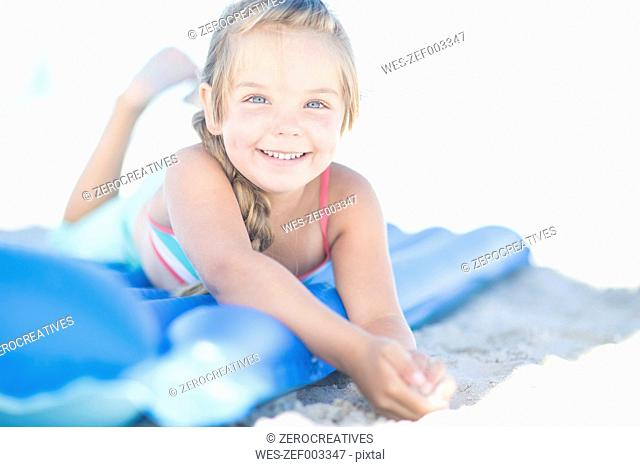 Smiling girl on beach lying on a lilo