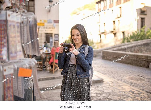 Spain, Granada, smiling young woman with camera at Albayzin district
