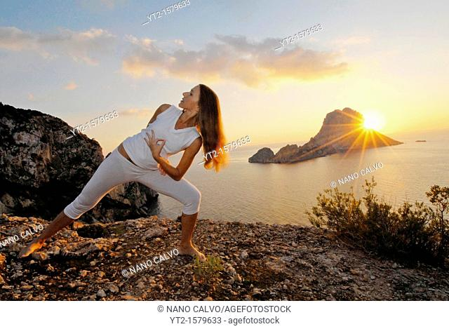 Yoga Teacher Lena Tancredi, doing yoga at sunset in Ibiza, with Es Vedra in view