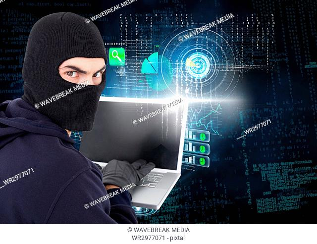 Hacker looking the lens and using a laptop in front of digital background