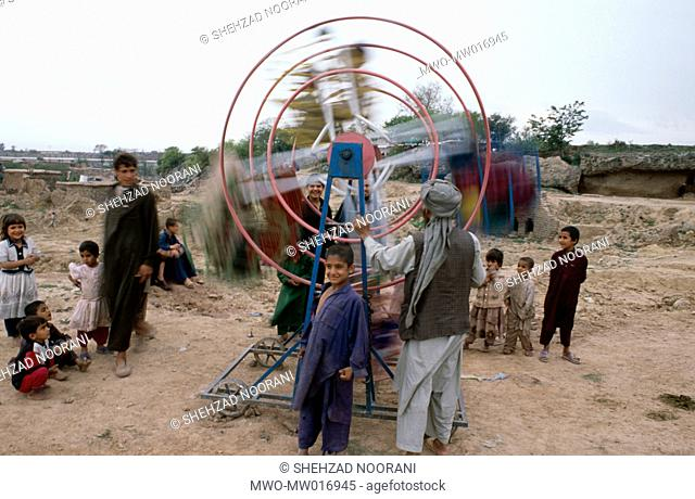 In a settlement of Afghan refugees, just outside the city of Islamabad, the capital, children ride Ferris Wheels Pakistan July 10, 2008