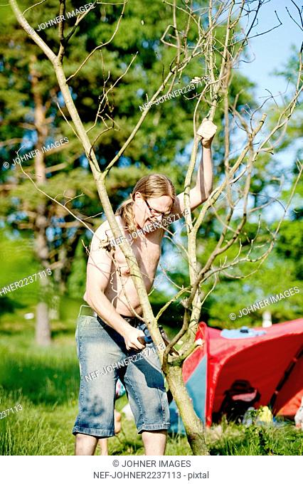 Man cutting branch