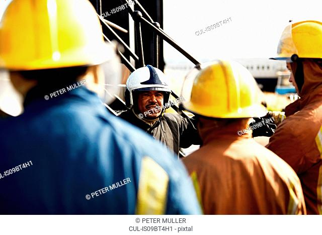 Firemen training, firemen listening to supervisor, over the shoulder view