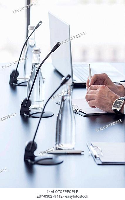 Microphones on table in conference room and business man hands