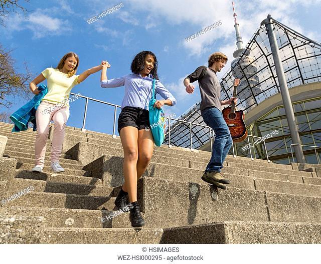 Germany, Bavaria, Munich, Three friends having fun at the Olympic Park