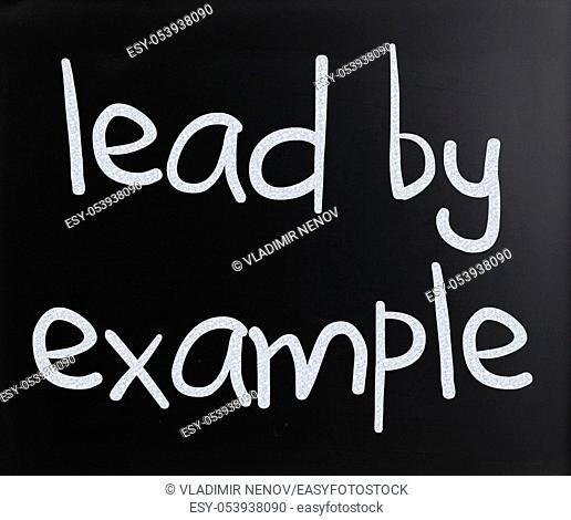 """""""""""Lead by example"""" handwritten with white chalk on a blackboard"