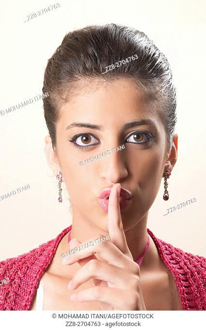 Young woman hand on mouth with silence gesture