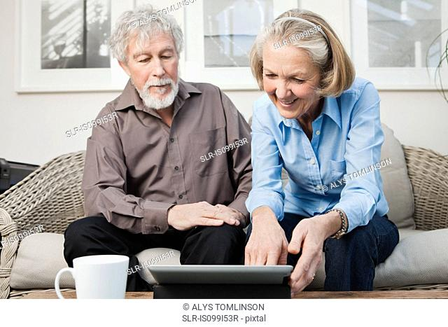 Senior couple with digital camera