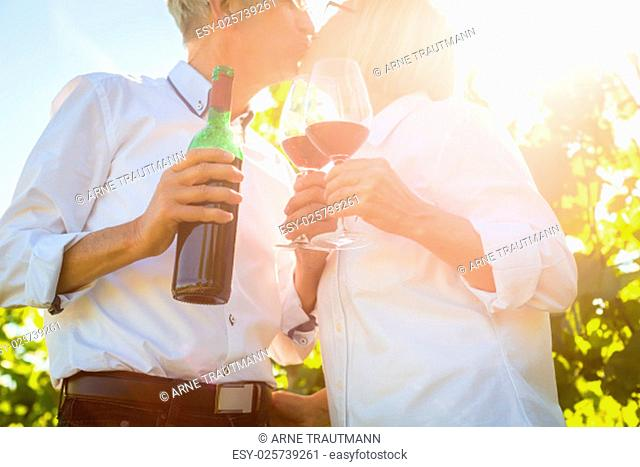 elderly couple enjoying red wine outdoors,man and woman send to another