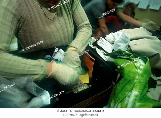 DEU, Germany, Duesseldorf : Baggage of a arrested drug dealer is searched by a police officer. Drug squad police officers