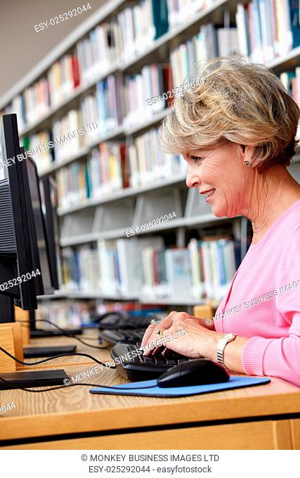 Senior woman working on computer in library