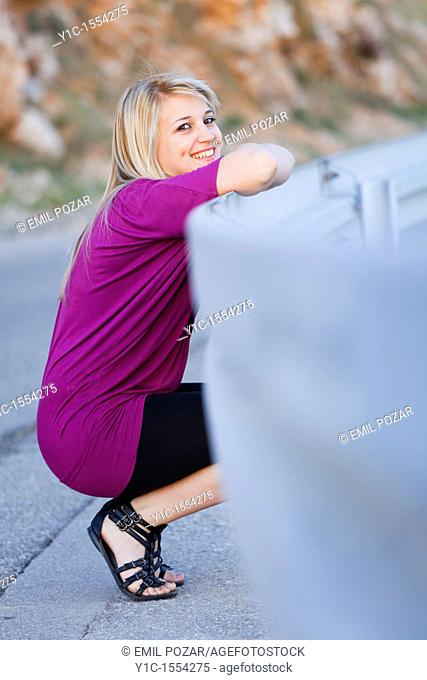Attractive young woman happy smiling smile squatting by the road