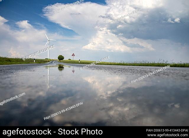 13 June 2020, Saxony, Waldenburg: The landscape is reflected in the wet country road after a rain shower. In the afternoon heavy thunderstorms are predicted for...