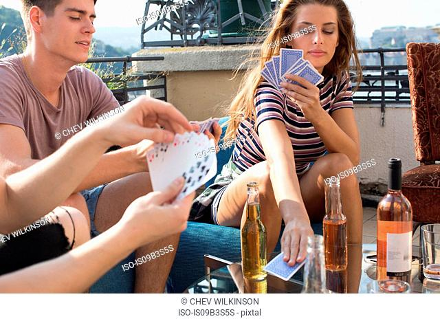 Young adult friends playing card games at roof terrace party