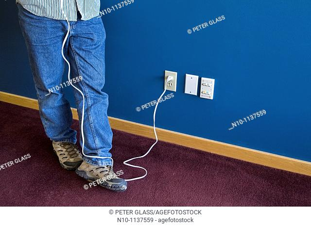 Man, from the waist down, holding an electrical object