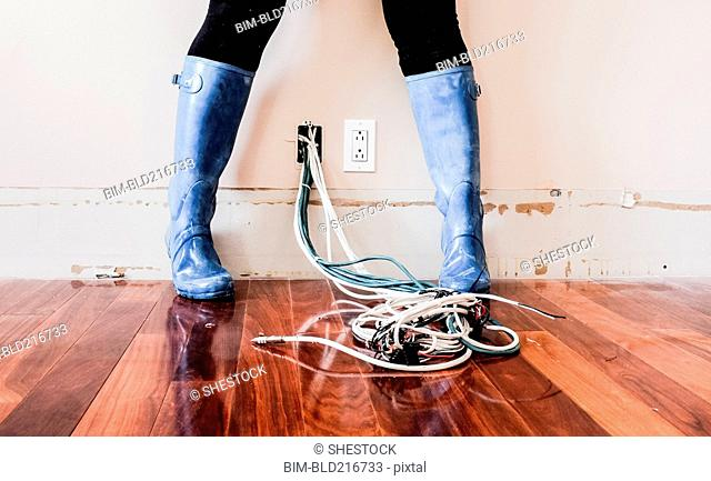 Caucasian woman wearing rain boots over electrical wiring