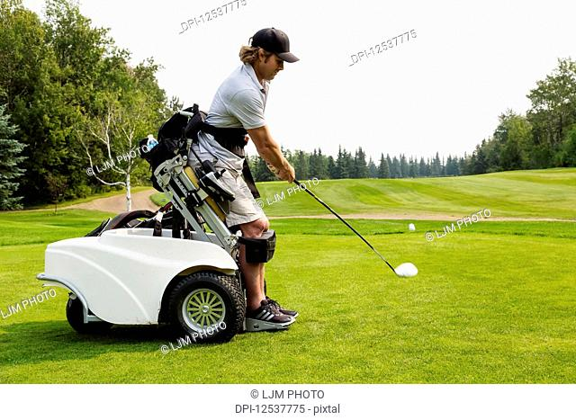 A physically disabled golfer driving a ball on a golf green and using a specialized golf assistance motorized hydraulic wheelchair; Edmonton, Alberta, Canada