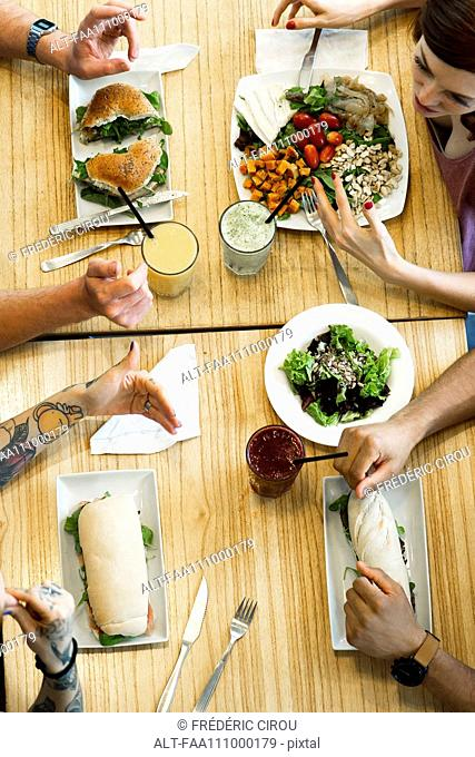 Friends dining in restaurant, cropped overhead view