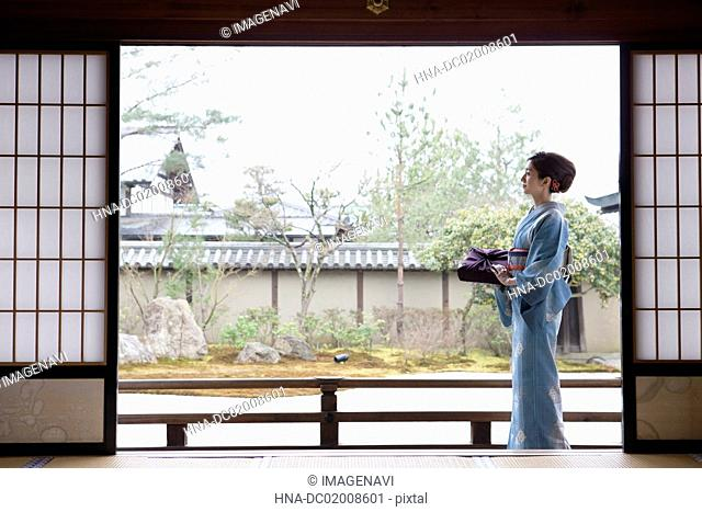 Young Japanese woman in kimono with parcel walking on porch