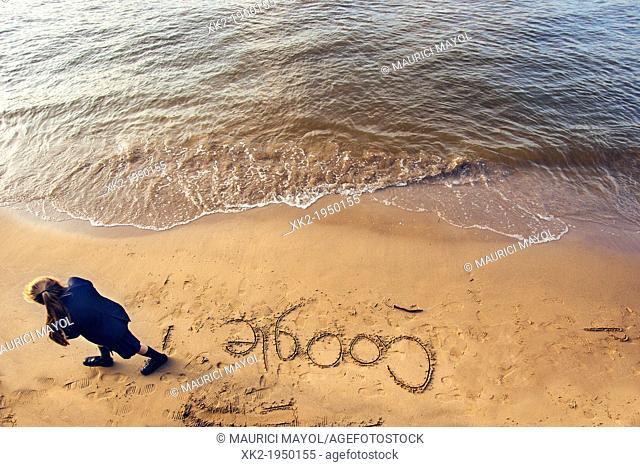 Schoolgirl writing GOOGLE in the sand