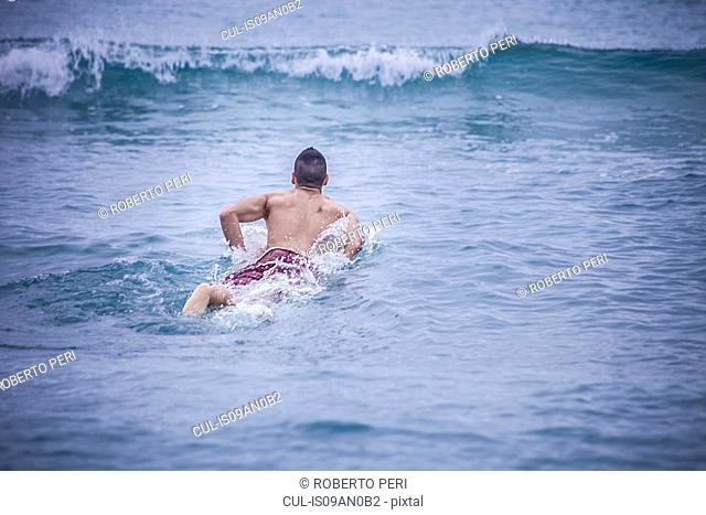 Young male surfer lying on surfboard in sea, Cagliari, Sardinia, Italy
