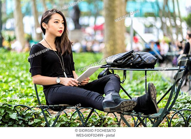 USA, New York, young woman with tablet sitting at city park